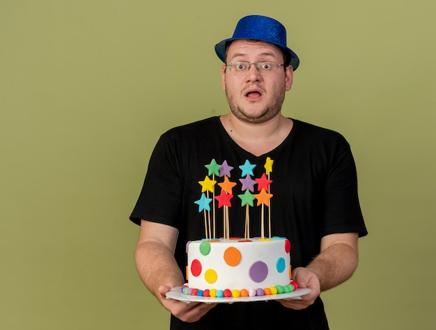 Impressed adult slavic man in optical glasses wearing blue party hat holds birthday cake