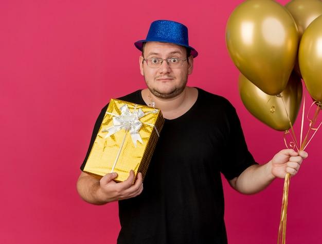 Impressionato uomo slavo adulto in occhiali ottici che indossa un cappello da festa blu tiene palloncini di elio e confezione regalo