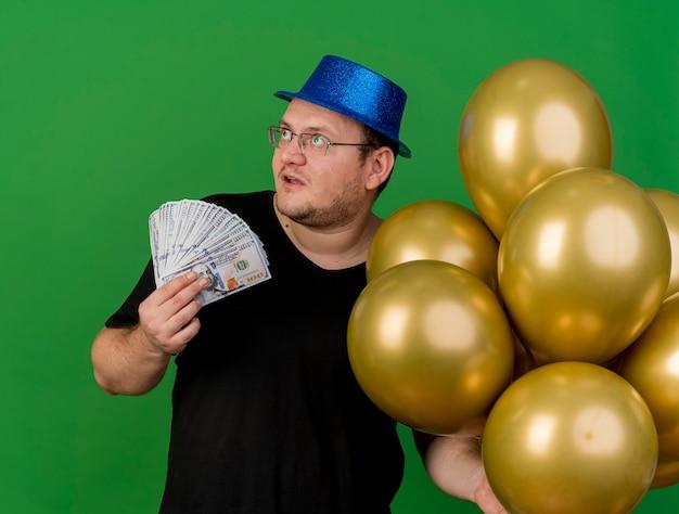 Impressionato uomo slavo adulto in occhiali ottici che indossa un cappello da festa blu tiene palloncini di elio e denaro guardando di lato