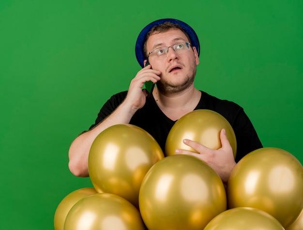 Impressionato uomo slavo adulto in occhiali ottici che indossa un cappello da festa blu tiene palloncini di elio che parlano al telefono