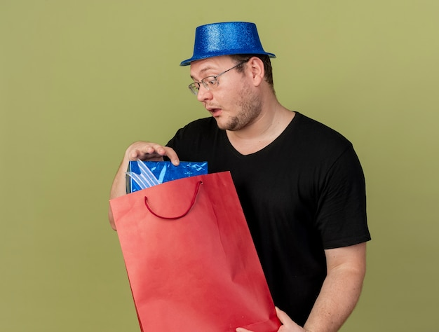 Impressed adult slavic man in optical glasses wearing blue party hat holds and looks at gift box in paper shopping bag