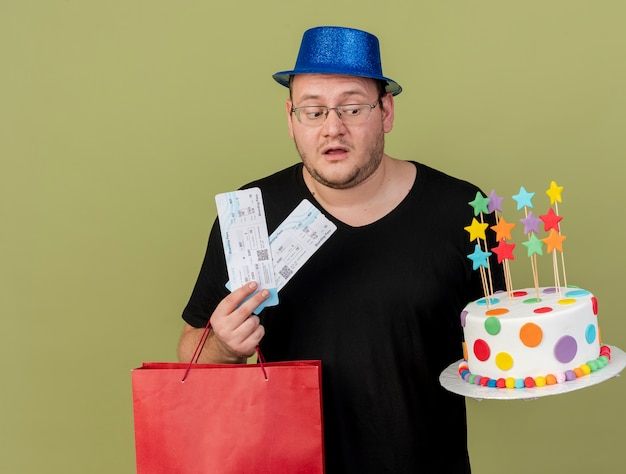 Impressed adult slavic man in optical glasses wearing blue party hat holds paper shopping bag birthday cake and air tickets
