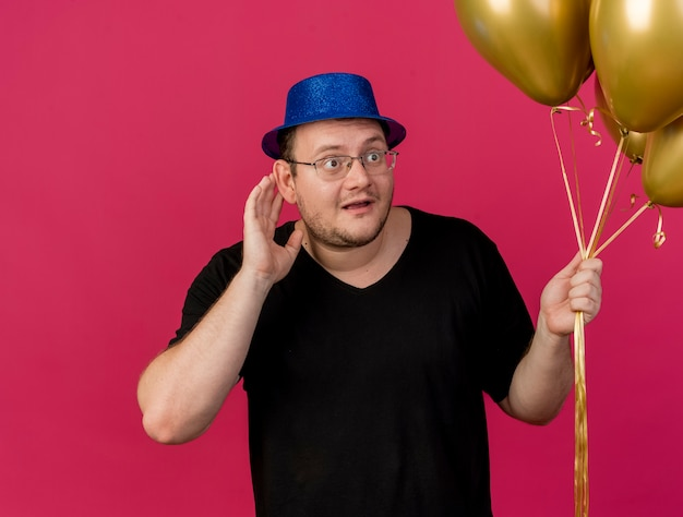 Impressionato uomo slavo adulto in occhiali ottici che indossa un cappello da festa blu tiene la mano vicino all'orecchio cercando di sentire e tiene palloncini di elio
