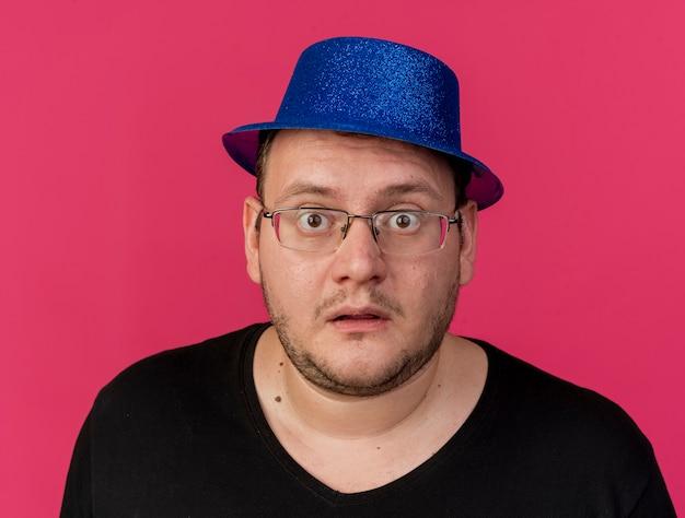 Uomo slavo adulto impressionato con occhiali ottici che indossa un cappello da festa blu