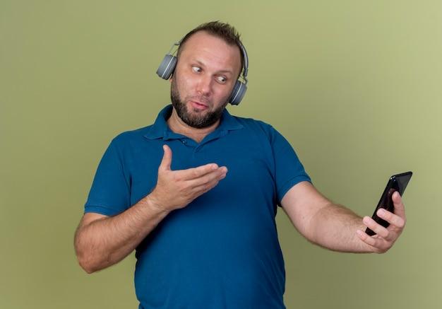 Впечатленный взрослый славянский мужчина в наушниках, держащий глядя и указывая рукой на мобильный телефон
