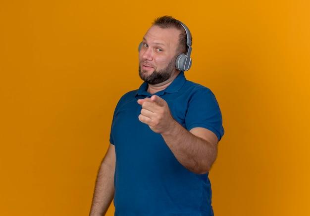 Впечатленный взрослый славянский мужчина в наушниках смотрит и указывает, слушая музыку