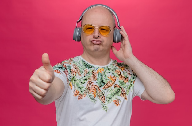 Impressed adult slavic man with sunglasses and on headphones thumbing up