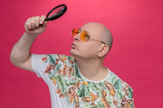Impressed adult slavic man with sunglasses holding and looking at magnifying glass
