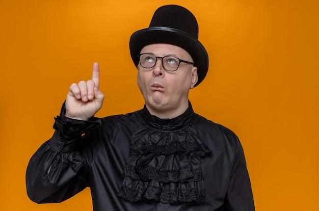 Впечатленный взрослый славянский мужчина в цилиндре и оптических очках в черной готической рубашке смотрит и указывает вверх