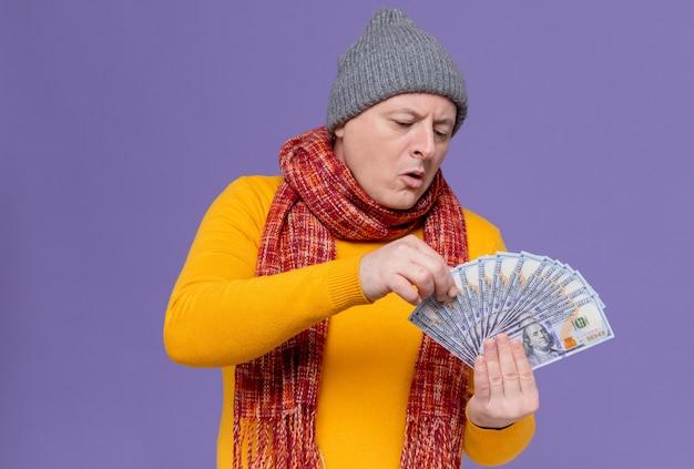Impressionato uomo slavo adulto con cappello invernale e sciarpa intorno al collo che tiene e guarda soldi