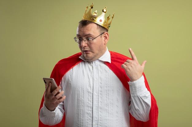 안경과 왕관을 착용하고 올리브 녹색 벽에 고립 된 손가락을 올리는 휴대 전화를보고 빨간 망토에 감동 된 성인 슬라브 슈퍼 히어로 남자