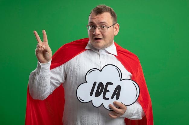 Впечатленный взрослый славянский супергерой в красном плаще в очках, держащий пузырь идеи, держащий пузырь идеи, делающий знак мира, изолированный на зеленой стене