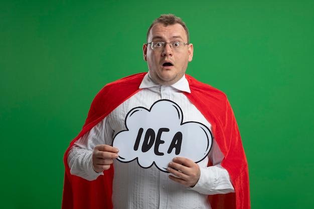 Впечатленный взрослый славянский супергерой в красной накидке в очках, держащий пузырь идеи, изолированный на зеленой стене