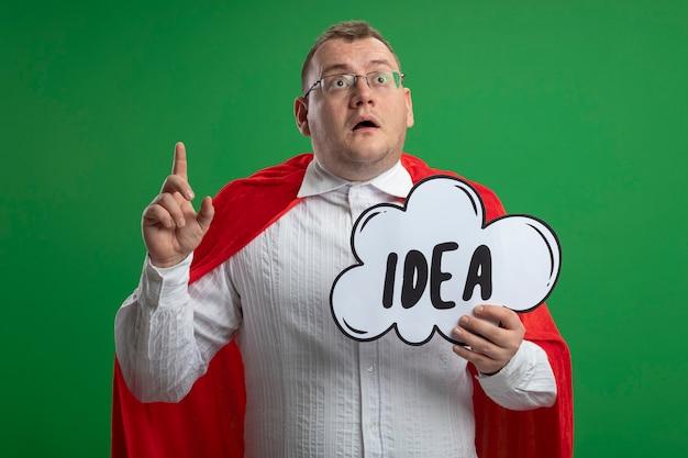 Впечатленный взрослый славянский супергерой в красной накидке в очках, держащий пузырь идеи, глядя вверх, поднимая палец, изолированный на зеленой стене