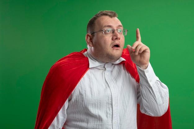 緑の壁に隔離されたまっすぐに指を上げる眼鏡をかけている赤いマントの印象的な大人のスラブスーパーヒーロー