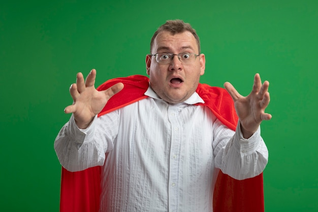 녹색 벽에 고립 된 손을 뻗어 안경을 쓰고 빨간 망토에 감동 된 성인 슬라브 슈퍼 히어로 남자