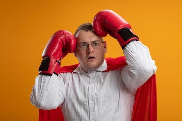 Impressionato uomo adulto supereroe slavo in mantello rosso con gli occhiali e guanti di scatola guardando il lato toccando la testa con le mani isolate sulla parete arancione