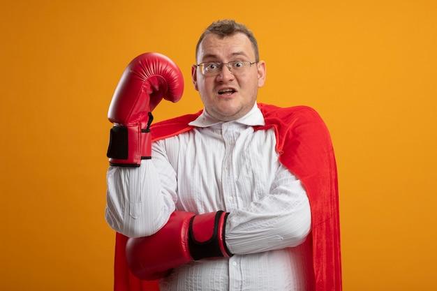 Impressionato uomo adulto supereroe slavo in mantello rosso con gli occhiali e guanti box mettere la mano sotto il braccio mantenendo un'altra mano in aria isolata sulla parete arancione