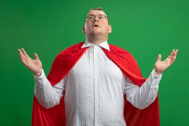 Impressionato uomo adulto supereroe slavo in mantello rosso con gli occhiali che mostra le mani vuote cercando isolato su sfondo verde