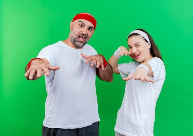 ヘッドバンドとリストバンドを身に着けている印象的な大人のスポーティなカップルは、両方の手を伸ばしています