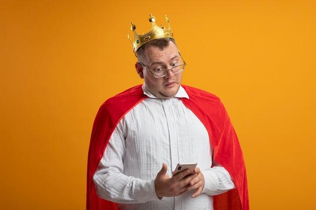 Uomo adulto del supereroe colpito in mantello rosso con gli occhiali e corona che tiene e guardando il telefono cellulare isolato sulla parete arancione