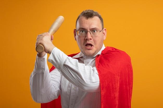 Uomo adulto del supereroe impressionato in mantello rosso con gli occhiali che tiene la mazza da baseball guardando la parte anteriore preparandosi a colpire isolato sulla parete arancione