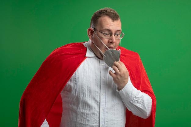 Impressionato uomo adulto supereroe in mantello rosso con gli occhiali e maschera protettiva guardando verso il basso cercando di togliersi la maschera isolata sulla parete verde