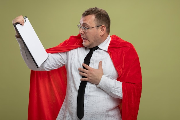Impressed adult superhero man in red cape wearing glasses and tie holding and looking at clipboard putting hand on chest isolated on olive green wall