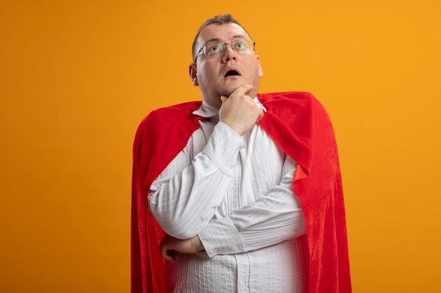 Impressed adult superhero man in red cape wearing glasses touching chin looking up isolated on orange wall