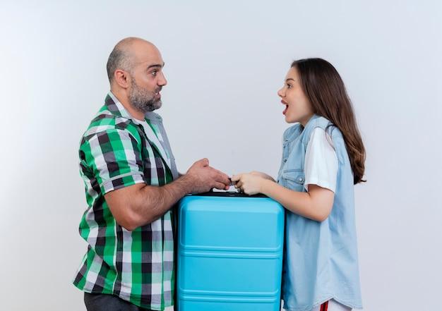 Impressionato coppia di viaggiatori adulti entrambi in possesso di valigia guardando a vicenda