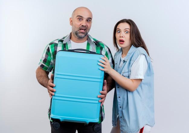 Uomo adulto delle coppie impressionate del viaggiatore che tiene la valigia e donna che mettono la mano sulla valigia entrambi alla ricerca