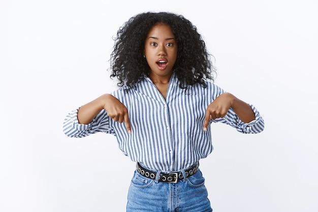 Impressionato modello femminile afroamericano che indossa camicetta da ufficio lascia cadere la mascella stupito trovando uno spazio di copia fantastico che mostra il prodotto pubblicitario promozionale allarga gli occhi eccitato in piedi divertito, muro bianco