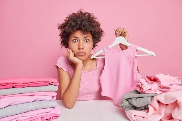Impressed afro american woman sorts clothes holds apparel on hanger selects clothing from wardrobe for donation in charity shop surrounded by laundry isolated on pink