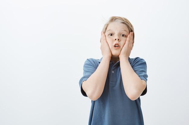 Впечатлил изумленный милый ребенок мужского пола в синей футболке, положив ладони на щеки, задерживая дыхание и задыхаясь от шока и удивления