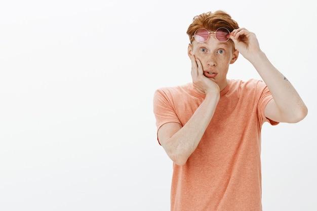 Impressed and amazed redhead man take-off sunglasses