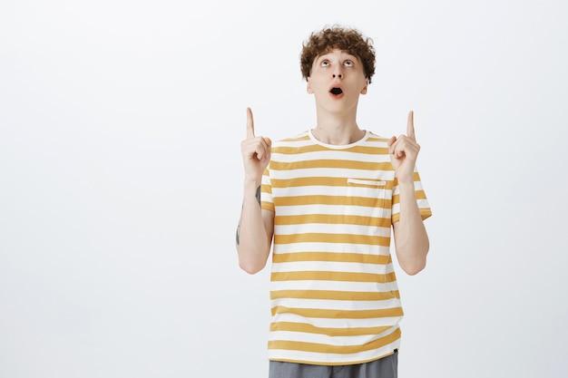 Ragazzo adolescente impressionato e stupito in posa contro il muro bianco