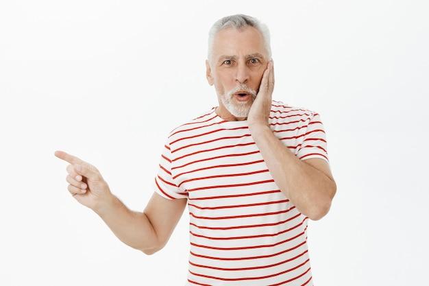 Впечатленный и изумленный старший мужчина, указывая пальцем влево, изумлен