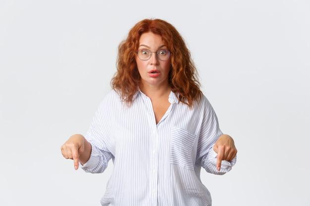 감동하고 놀란 중년의 빨간 머리 여성은 굉장한 뉴스에 반응하여 손가락을 아래로 가리키고 헐떡이며 흥분, 흰 벽에서 숨을 참습니다.