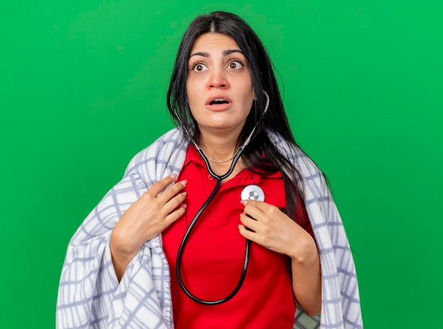 Впечатленная и сконцентрированная молодая больная женщина со стетоскопом, завернутая в плед, слушает биение своего сердца, глядя в сторону, изолированную на зеленой стене