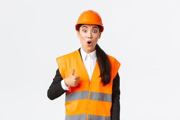 安全ヘルメットと反射ジャケットの印象的で興奮したアジアの女性エンジニアは、素敵な仕事に魅了され、親指を立ててあえぎながら驚いて、よくやった、素晴らしい仕事、立っている白い背景を示しています
