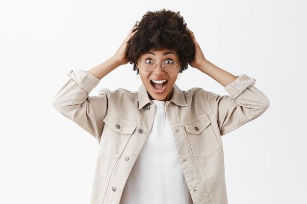 アフロの髪型が髪に触れ、幸せから叫び、驚きと驚きを感じるベージュのシャツを着た、印象的で興奮している見栄えの良い暗い肌の女性写真家