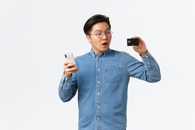 Впечатленный и очарованный азиатский парень, изумленно смотрящий на кредитную карту, используя смартфон, оплачивая онлайн-заказ, удивленный новым приложением электронного банкинга, стоящим на белом фоне.