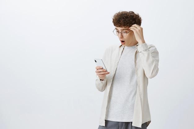 흰 벽에 포즈를 취하는 감동과 충격을받은 십대 남자