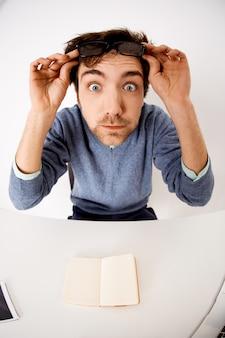 Впечатленный и удивленный молодой удивленный человек снимает очки, высунул глаза, сидя на офисном столе