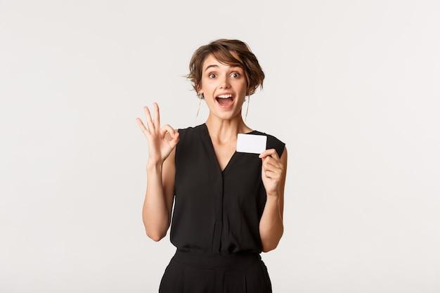 Впечатлил привлекательную коммерсантку показывая нормальный жест и кредитную карту, стоя над белизной.