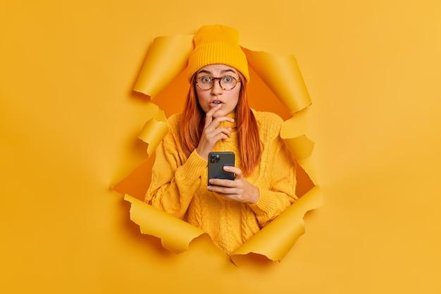 La donna attraente rossa impressionata trattiene il respiro e utilizza lo smartphone legge notizie scioccanti naviga sui social network di internet vestiti con un caldo cappello di maglia lavorata a maglia.