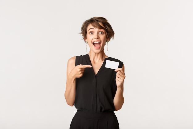 Впечатленная привлекательная женщина, говорящая о кредитной карте, стоя белой.
