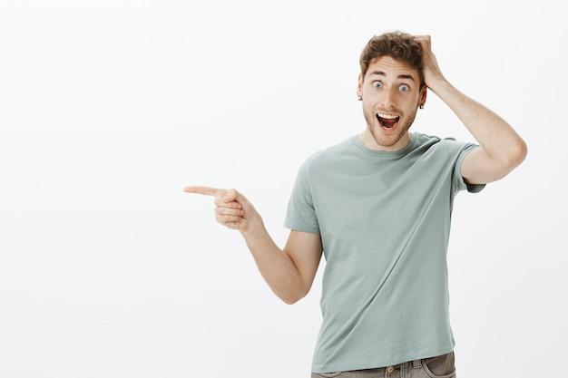 Впечатленный привлекательный молодой человек чувствует себя удивленным и счастливым, видя удивительные вещи, держится за голову и кричит с улыбкой, указывая влево