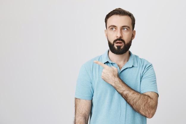 Впечатленный бородатый мужчина с открытым ртом возбужден и указывает в левый верхний угол
