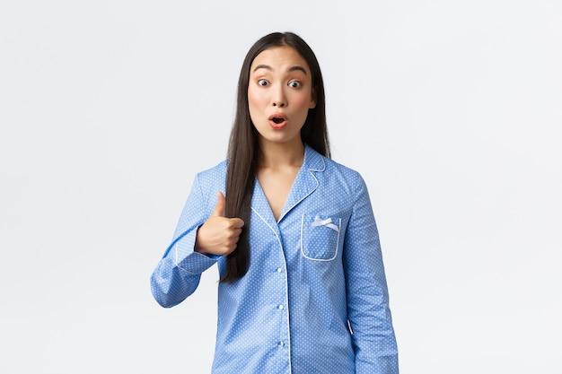青いパジャマを着た美しいアジアの女の子が親指を立てて、素晴らしい寝坊、素晴らしいスキンケア製品、またはプロモーションに驚いています。サポートを示している女性は、素晴らしいものをお勧めします。